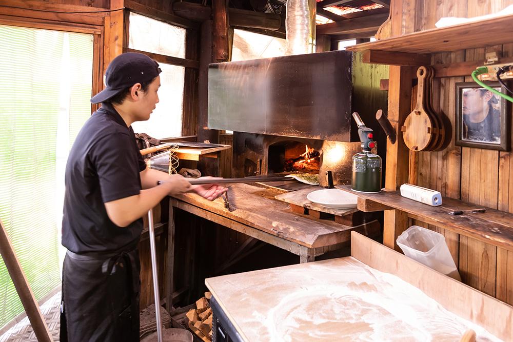 薪窯へピザを入れる